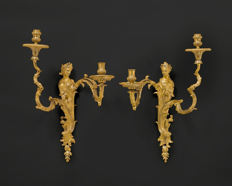 A pair of Règence two-light wall-lights, almost certainly after a design by Gilles-Marie Oppenord, Paris, date circa 1730